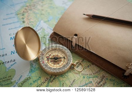 male hands holding a compass over the map and something is going to record in the notebook