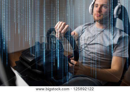 technology, gaming, entertainment, let's play and people concept - close up of young man in headphones with pc computer playing car racing video game at home and steering wheel