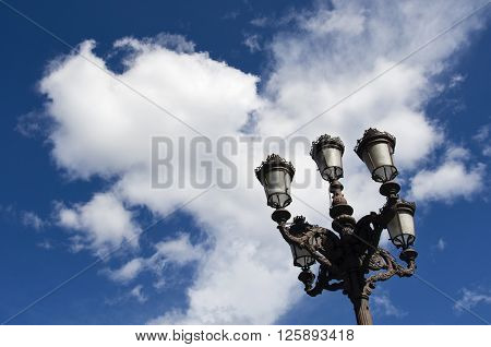 Old street lamps in front of a clear blue sky and white clouds