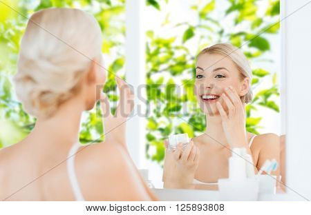 beauty, skin care and people concept - smiling young woman applying cream to face and looking to mirror at home bathroom over green natural background