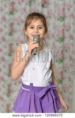 Beautiful little girl with microphone at home