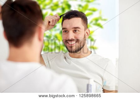 beauty, grooming and people concept - smiling young man looking to mirror and brushing hair with comb at home bathroom over green natural background
