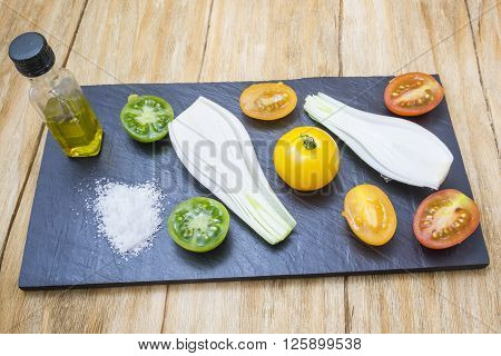 red tomatoes, yellows, greens and spring onions with salt and oil shale above a tray on a wooden table