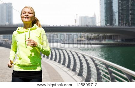 fitness, sport, people and healthy lifestyle concept - happy young woman jogging over dubai city street or waterfront and bridge background