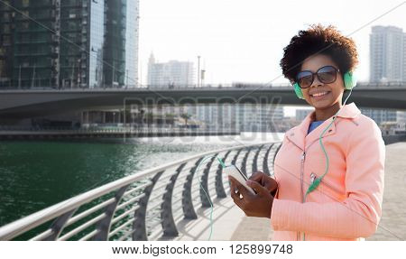 technology, lifestyle and people concept - smiling african american young woman with smartphone and headphones listening to music over dubai city street or waterfront and bridge background