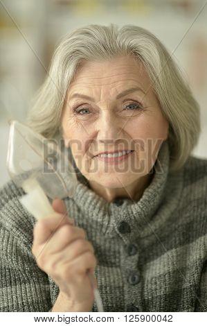 Portrait of elderly woman with flu inhalation