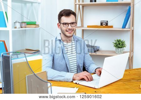 IT company. Young programmer working with laptop. Nice office interior. Professional coder looking at camera and smiling