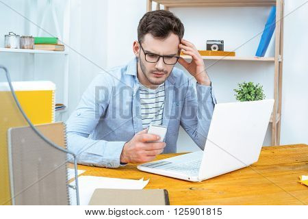IT company. Young programmer working with laptop. Nice office interior. Professional coder using mobile phone