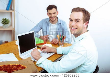 IT company. Young programmers working with laptop with pizza. Nice office interior. Professional coders looking at camera and smiling