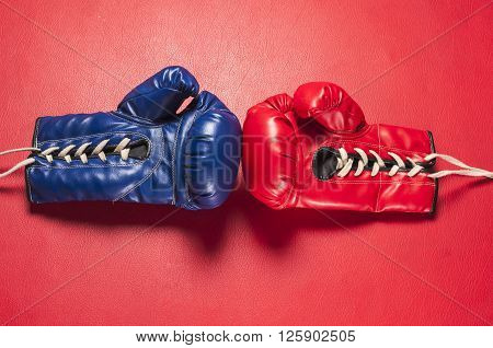 Boxing series : Blue and red boxing gloves on red leather background