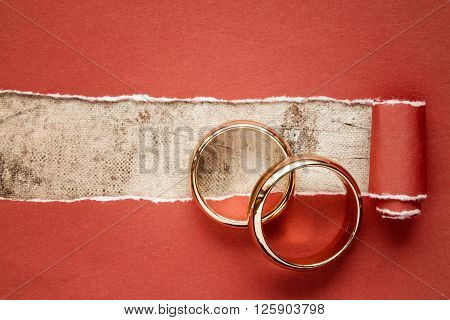 Torn red paper and two gold wedding rings