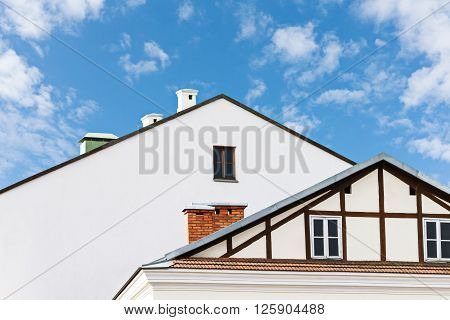 Roofs Of Residential Buildings Against Blue Sky