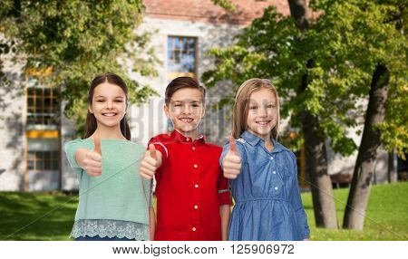 childhood, education, holidays, gesture and people concept - happy smiling boy and girls showing thumbs up over campus and summer park background