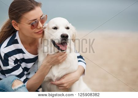 Portrait of young beautiful woman in dark glasses,brunette with beautiful smile,wearing a striped t-shirt and blue jeans, sitting on a sandy beach against the blue of the ocean,hugging a beloved friend - a dog breed Golden Retriever