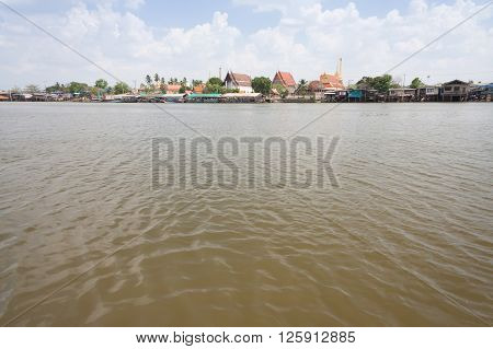 Chao Phraya river in Bangkok Thailand with temple and thai houses in the background.