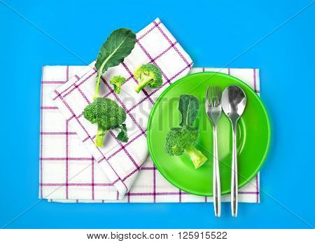 the top view of fresh broccoli in green dish and towel on vibrant color background healthy food concept