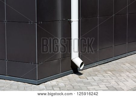 White Downspout On Dark Building Facade