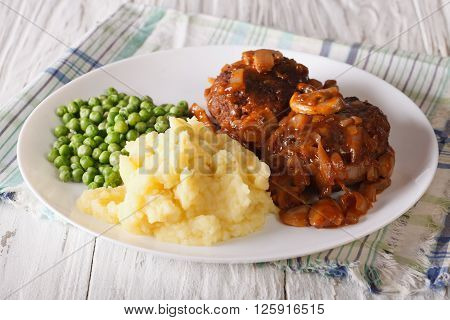 Salisbury Steak With Potatoes And Green Peas Close-up On A Plate. Horizontal