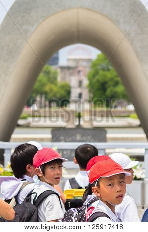 Hiroshima, Japan - July 10, 2014: A group of Japanese school children visits the Memorial Cenotaph in the center of Hiroshima Peace Memorial Park which holds the names of all of the people killed by the Atomic Bombing of Hiroshima in 1945.