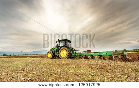 Karlovo Bulgaria - August 22th 2015: Ploughing a field with John Deere 7230R tractor. John Deere 8100 was manufactured in 1995-1999 and it has JD 7.6L or 8.1L 6-cyl diesel engine.