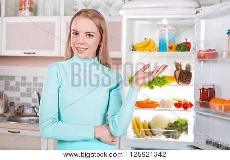 Pretty blonde standing near open fridge full of food. Young woman looking at camera, smiling and pointing at fridge
