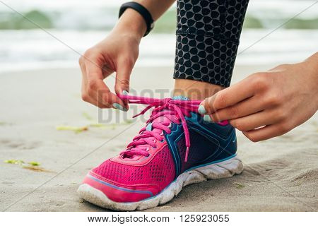 Female Hands With Manicure Tie Laces On Pink And Blue Sneakers On The Beach Close Up