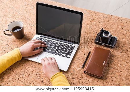 Businessman typing, coffee, wallet and vintage camera around. Cork table only hands seen. Concept of work.