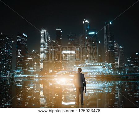 Rear view of businessman looking at nighttime Singapore cityscape
