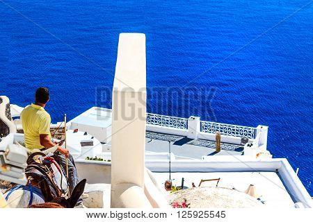 SANTORINI, GREECE-OCTOBER 13, 2015: White terraced houses overlooking the deep blue Aegean Sea in Santorini, Greece