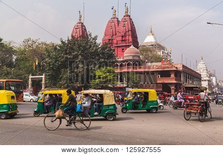 DELHI INDIA - 19TH MARCH 2016: A view of streets and the Shri Digambar Jain Lal Mandir Temple in Delhi. Lots of Tuk Tuk Rickshaws and traffic can be seen.
