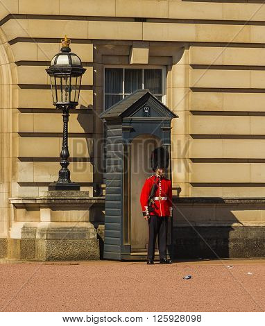 LONDON UK - 18TH JULY 2015: A Royal Guard outside Buckingham Palace during the day. Weather the red summer garment
