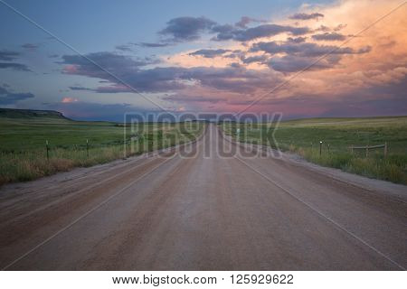 The clouds light up at sunset along a gravel and dirt road in Douglas County Colorado in the summer