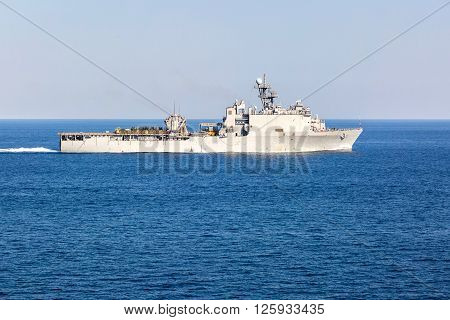 Grey warship supplier is underway in the sea.