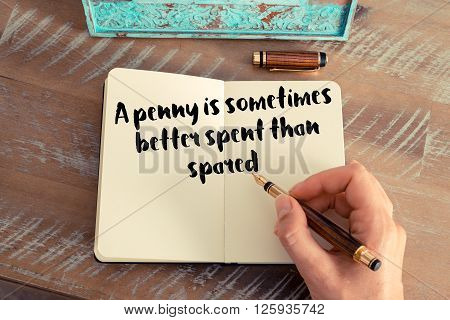 Handwritten quote A penny is sometimes better spent than spared, as inspirational concept image