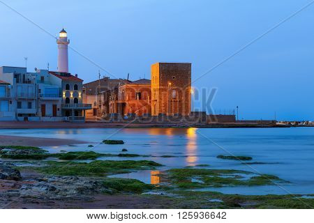 Dawn at Punta Secca Beach with the lighthouse and the watchtowerTorre Scalambri in Santa Croce Camerina Sicily Italy