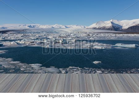 Opening wooden floor, Jokulsarlon ice lake with snow mountain background, Iceland, natural landscape