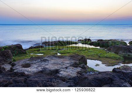 Sunset at Punta Secca Beach with rocks and green seaweeds in Santa Croce Camerina Sicily Italy
