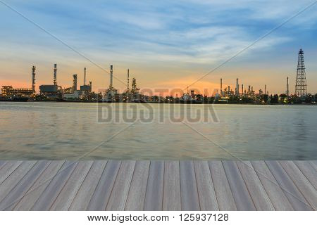 Opening wooden floor, Petroleum Refinery plant river front during sunrise
