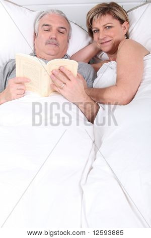 Couple laid in a bed reading a book