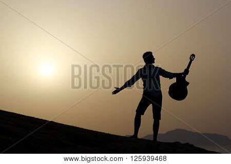 happy guitarist dark silhouette at sunrise holding guitar up in the air