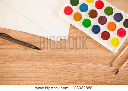 Artist's workspace. Set of 18 watercolor paints in white base 2 sheets of white watercolor paper 2 brushes pen on light woden background. Artistic background.