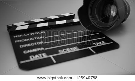 Cinemas clapperboard with camera lens on it in monochrome color