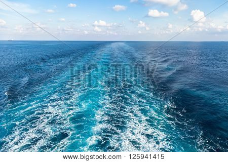Wake on blue sea surface under cloudy sky.
