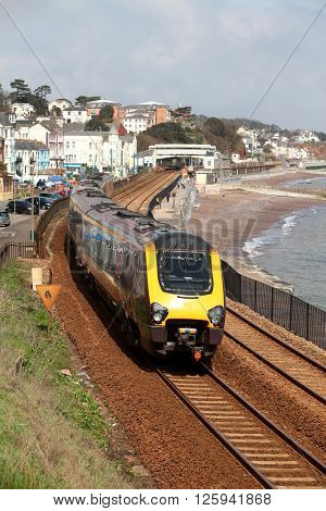A diesel locomotive leaves Dawlish station showing the beach and town behind