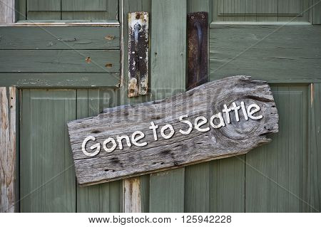 Gone to Seattle sign on old green doors.