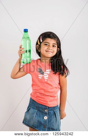 indian girl opening cold drink bottle, asian girl drinking cold drink in pet bottle, girl kid and cold drink, indian cute girl with lemon or carbonated cold drink in plastic bottle, isolated on blue