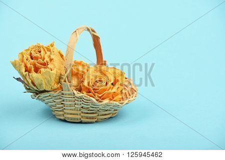 Dried Roses In Wicker Basket Over Blue