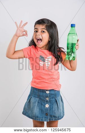 indian girl with cold drink bottle, asian girl drinking cold drink in pet bottle, girl kid and cold drink, indian cute girl with lemon or transparent juice in plastic bottle, isolated on white