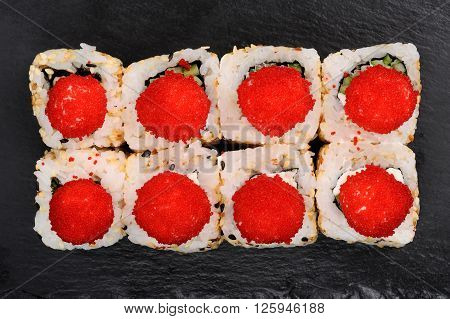 Set of fusion rolls with sesame seeds decorated with red caviar overhead view