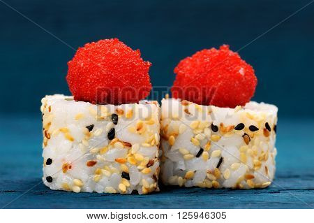 Yummy Japanese fusion rolls with sesame seeds topped with red roe closeup